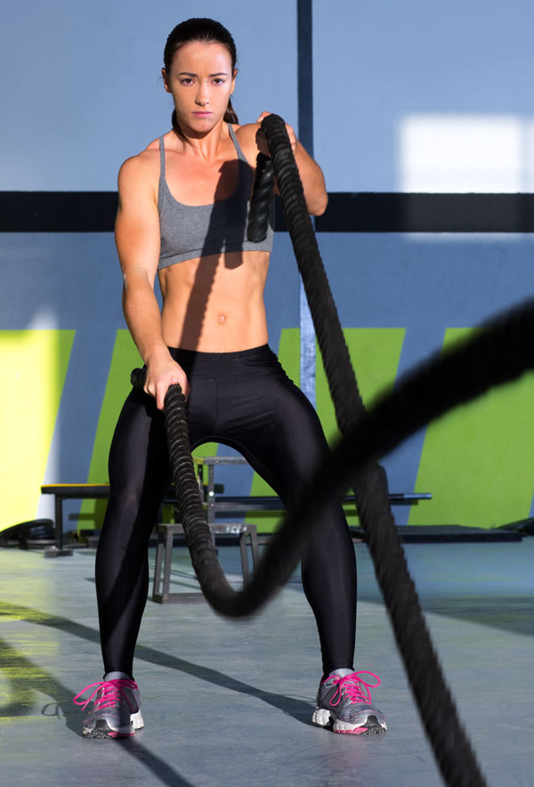 A woman using crossfit battle ropes